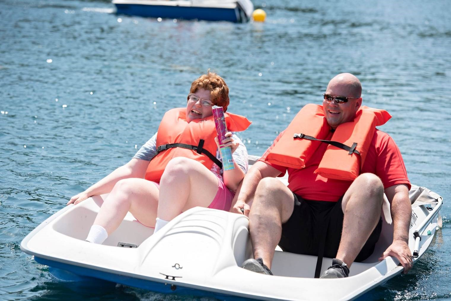 Man and woman laughing on a paddle boat