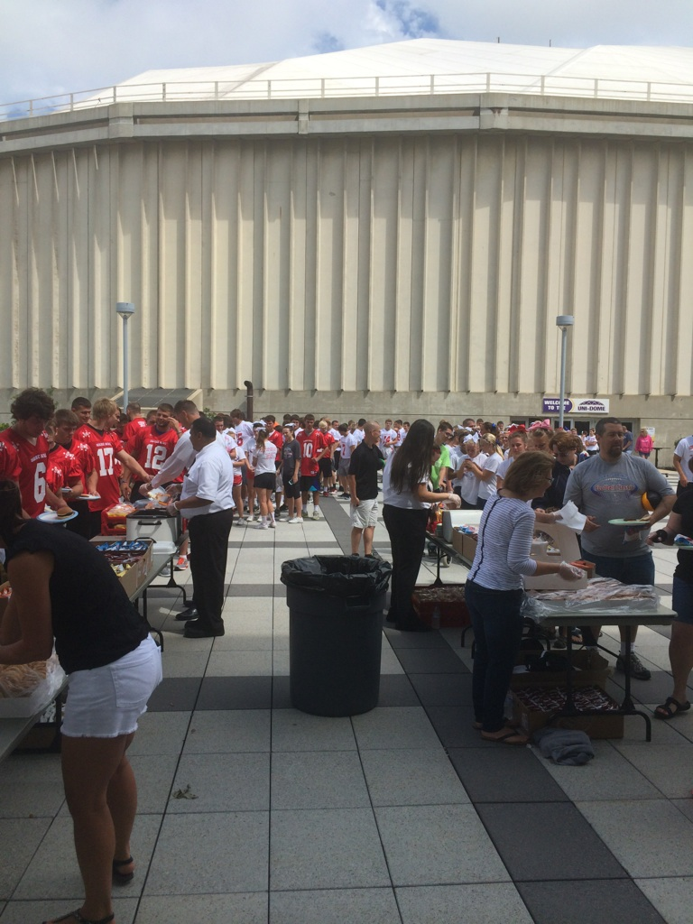 Shrine Bowl players and kids line up to eat.