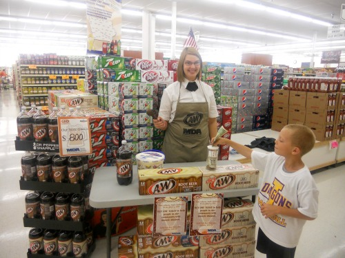 Child makes donation for a root beer float served by a Fareway employee.