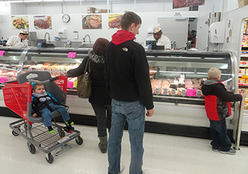 Family shopping in Fareway Clinton store utilizing special needs cart