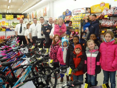Fareway employees standing with children next to their newly gifted bikes