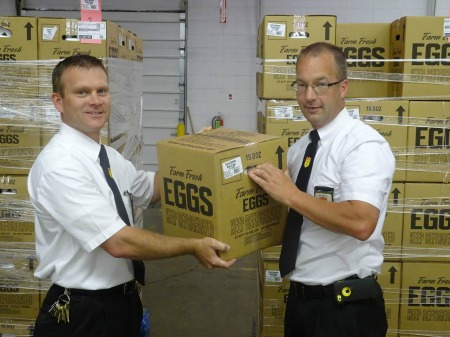 Fareway employees unloading boxes of eggs off of a pallet