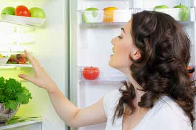 Image of woman going through her kitchen fridge.