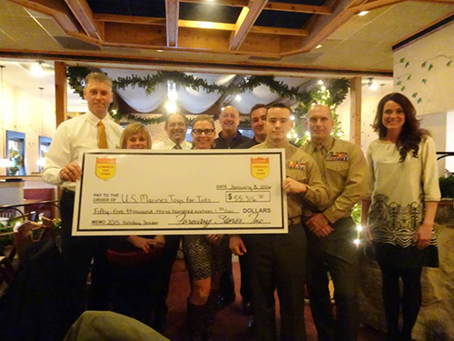 Fareway employees hold up oversize check for Toys for Tots.